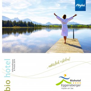 The title page of the German hotel brochure of the Biohotel Eggensberger 2019, on which a photo of a woman standing on a jetty is printed.